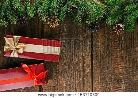 Christmas frame of evergreen twigs with gift boxes on old brown wood. Overhead view