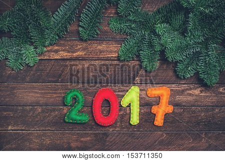 2017 made of felt and Christmas tree. Childish New year background with christmas toy from felt on dark rustic wooden background. Holiday card - 2017 happy new year!