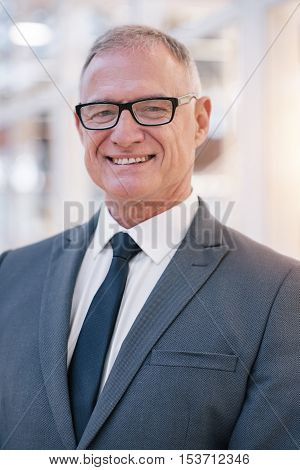 Portrait of a smiling mature businessman in glasses standing in the lobby of a modern office building