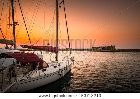 Boats in old venetian  port of Chania at sunset. View of the old venetian harbor of Chania on Crete island, Greece.
