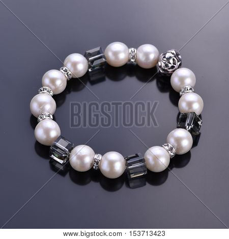 Pearl bracelet with crystals on a dark background. Beadwork. Top view.