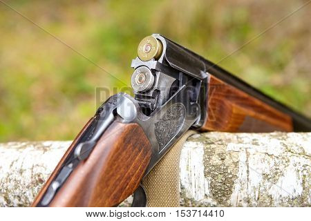 Opened wooden double-barreled hunting gun with two cartridges