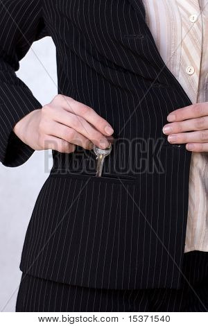 Businesswoman putting a key into her pocket