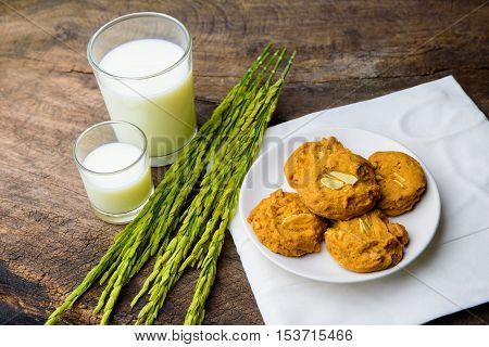 Almond Cookies with rice milk and ear of rice on old wooden table for breakfast for vegetarian festival background.