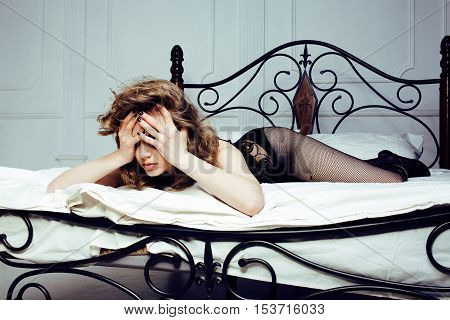 crying woman laying in bed, winter depression holding head with hands, having hangover close up