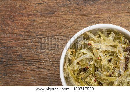 a small ceramic bowl of seaweed salad based on agar-agar against rustic wood