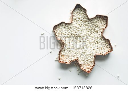 Over head flat lay view of copper cookie cutter filled with white sprinkles spilling over against white background.