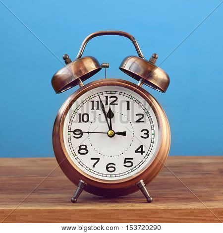 Retro the alarm clock of bronze color at twelve o'clock on a blue background. Midnight midday. Minutes about New year.