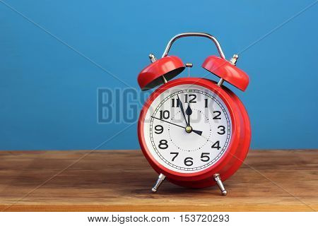 Red retro alarm clock at twelve o'clock on a blue background. Midnight midday. Minutes about New year.
