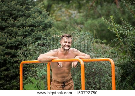 fitness, sport, exercising, training and lifestyle concept - young man doing triceps dip on parallel bars outdoors