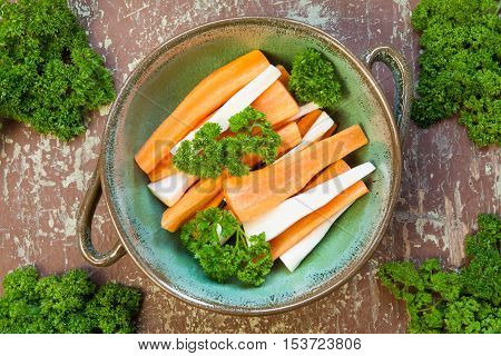 Parsley and carrots garnished with green leaf in a bowl