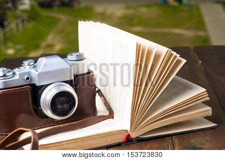 Open book and vintage camera on table. Copy space