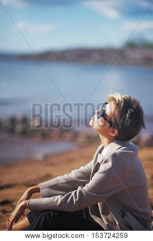 Brooding stylish girl in fashion clothing and dark glasses sitting on the rocks tired