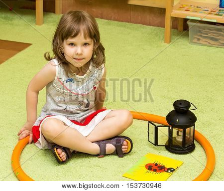 Cute little girl sitting on the floor in Montessori kindergarten . The girl folded her Turkish legs . She looks directly into the camera.
