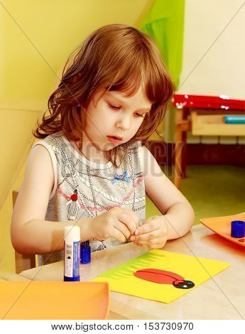 Pensive little girl in Montessori kindergarten makes applique . Girl sitting at the table in front of her with glue and a sheet of paper.