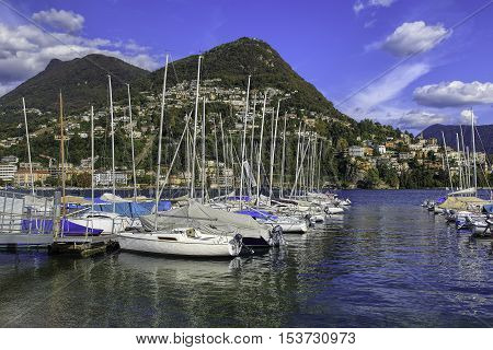 Lugano, Switzerland - 12 October, 2016: view on Lake Lugano, Monte Bre and Monte Boglia mountains in the background. Lake Lugano is a glacial lake on the border between southern Switzerland and northern Italy.