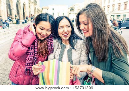 Cheerful girlfriends looking inside shoppìng bag - Group of young women on winter holiday standing at city central square smiling and showing gifts - Concept of leisure and friendship