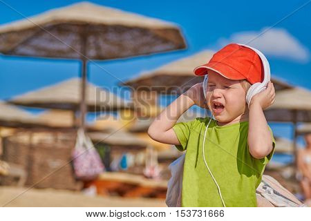 Happy emotional Child Boy Enjoying Music in Headphones at the Beach