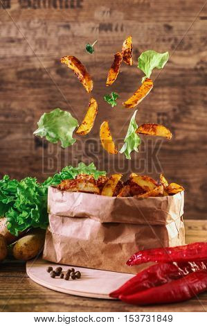 Flying slices of baked potato on wooden background.