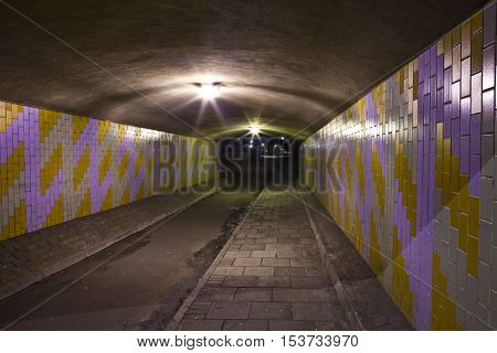 A night-time view of an eerie urban underpass or tunnel.