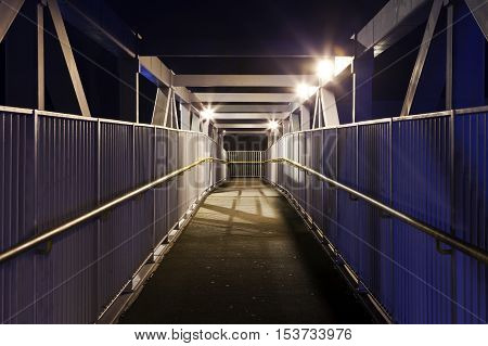 A night-time view of an eerie urban foot bridge.