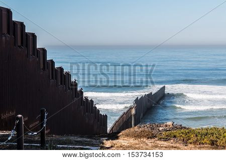 International border wall extending out into the Pacific ocean and separating San Diego, California from Tijuana, Mexico.