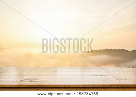 Empty top of wooden table over sea of mist over blurred mountain background. For display of your product warm morning