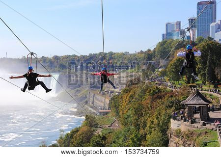NIAGARA FALLS, ONTARIO - OCT 12,2016. Here we see people on the new zipline ride known as Wild Play's Mist Rider. On a hot October day they will descend the escarpment to a platform below near the Horseshoe Falls.
