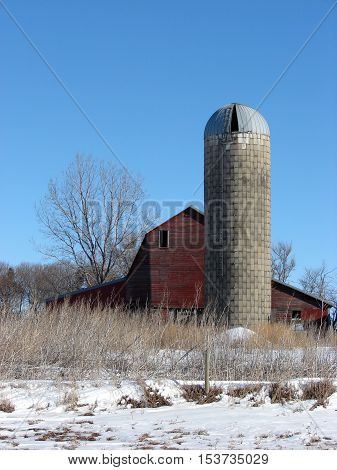 An old abandoned barn and Silo against a clear blue sky.