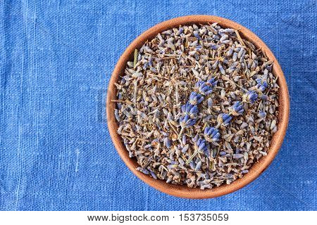 Ceramic bowl of lavander on blue fabric background. Top view.