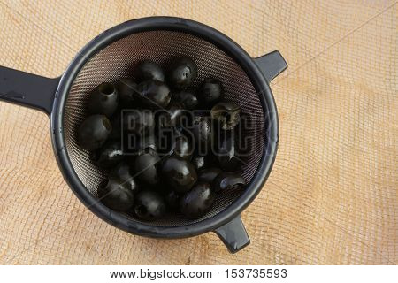 Rinsed Canned pitted black olives in strainer n bowl