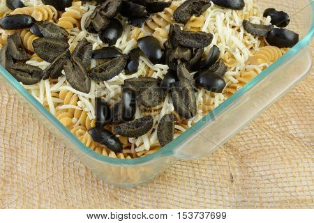 Casserole preparation of whole what rotini pasta, shredded mozzarella cheese and sliced black olives