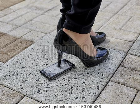 Black patent leather spiked heel womans shoe stepping on a cell phone