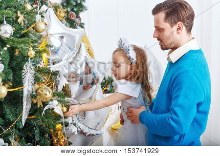 Daughter and father decorate Christmas tree. Father supports daughter and little cute girl hangs balls on the Christmas tree. The festive mood. Family celebration.