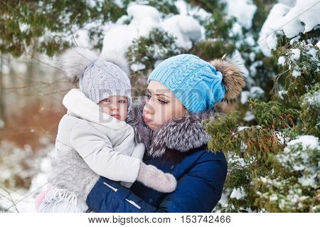 Mother and young daughter embracing in a winter park. Mother and daughter in her arms. Happy family. Childhood and parenthood happiness. Mother and daughter cheated her cheeks. Resentment.