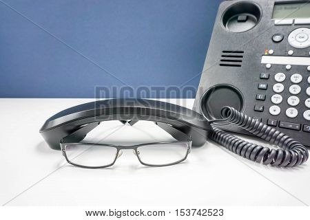 men glasses on the office dek with IP phone hang on