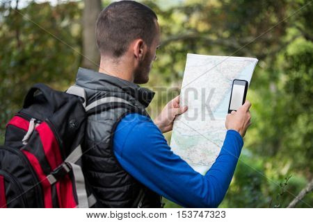 Male hiker looking at map and mobile phone in forest