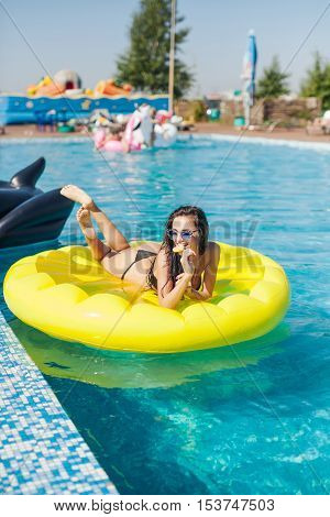 Sexy woman in bikini enjoying summer sun and tanning during holidays in pool with lolly pop