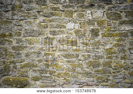 Part of a stone wall for background or texture.Old stone wall texture. Beautiful grey stone wall background with moss and darken edges. Stone wall background for banners, flyers and design