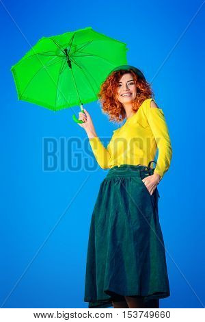 Pretty joyful young woman with beautiful foxy hair posing with umbrella over blue sky. Bright colorful clothes. Beauty, fashion. Bright lifestyle. Copy space.