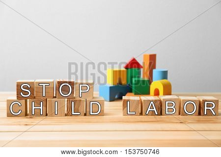 Cubes with words STOP CHILD LABOR and toys on light background