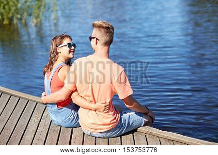 holidays, vacation, love and people concept - happy teenage couple sitting and hugging on river berth at summer