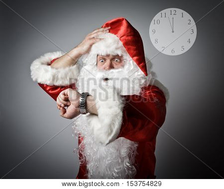Santa Claus is looking at his wristwatch. It's almost twelve o'clock. Concept of being late.
