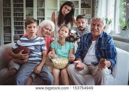 Unhappy multi-generation family watching soccer match on television in living room at home
