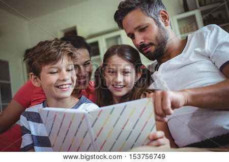 Smiling family looking at a photo album at home