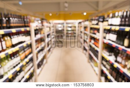 sale, shopping, consumerism and alcohol concept - liquor store blurred out of focus background with bokeh