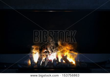 heating, warmth and fire concept - flame of firewood burning in modern fireplace