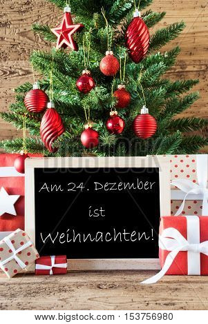 Colorful Christmas Card For Seasons Greetings. Christmas Tree With Balls. Gifts Or Presents In The Front Of Wooden Background. Chalkboard With German Text Weihnachten Means Christmas