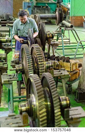 Tyumen, Russia - November 14, 2007: JSC Tyumenskie Motorostroiteli. Plant on production and repair of aviation engines. Mechanic works with part of aviation engine