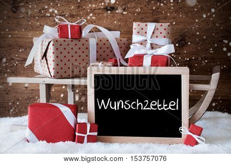 Chalkboard With German Text Wunschzettel Means Wish List. Sled With Christmas And Winter Decoration And Snowflakes. Gifts And Presents On Snow With Wooden Background.